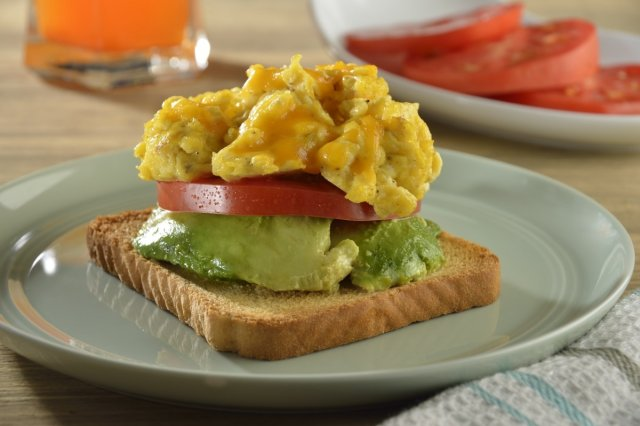 Toasted bread with avocado, tomato and egg with cheddar cheese
